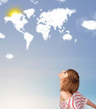 Girl looking at world clouds and sun on blue sky Stock Photo