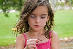 Girl Looking at a Worm. Young girl looking at a worm she is holding up stock images