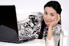 Girl looking at you with a computer laptop on bed Royalty Free Stock Photos