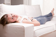 Girl looking you and smiling while lying on a sofa Stock Photography