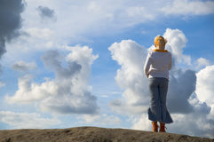 Girl on lookout. Girl on look out on hilltop against sky with big clouds stock photos
