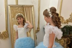 Girl Looks At Her Reflection In The Mirror Stock Photo