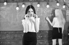 Girl looks attractive while lady writing on chalkboard background, defocused. Students and trainees concept. Student stock images
