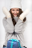 Girl looks from behind fur mittens Stock Image