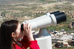 Girl looks through binoculars Royalty Free Stock Image