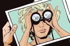 Girl looks through binoculars. Her hair fluttering in the wind. Stock Photo