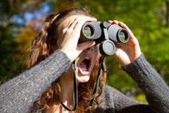 Girl looks through binoculars at schocking scene. Girl expresses shock and disbelief at a site she is viewing Stock Photos