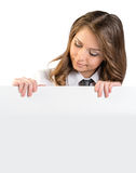 The girl looks at a blank white poster Stock Photography