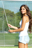 Girl looks through blinds Royalty Free Stock Image