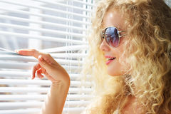 girl looks through the blinds Stock Photo