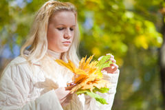 Girl looks at a bouquet of yellow leaves Stock Image