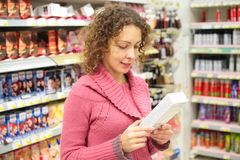 Girl looks at box with goods in hands Royalty Free Stock Photos