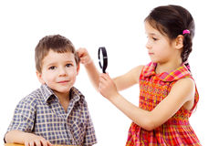 Girl looks to boy's ears through magnifier Stock Photos