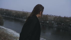 The girl looks at the bridge on the river during snowfall stock video footage
