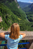 The girl looks from the bridge to the canyon Stock Photography
