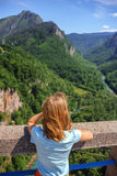 The girl looks from the bridge to the canyon Royalty Free Stock Photography