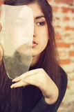 Girl looks through the broken glas Stock Images