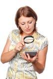 Girl looks at the calculator through a magnifier Stock Photos