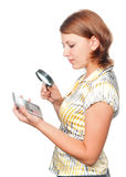 Girl looks at the calculator through a magnifier Royalty Free Stock Photography