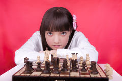 Girl looks at camera during chess. Royalty Free Stock Photo