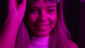 The girl looks at the camera, takes off and puts on sunglasses. Neon light.  stock video footage