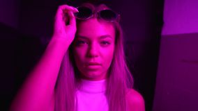 The girl looks at the camera, takes off and puts on sunglasses. Neon light.  stock footage