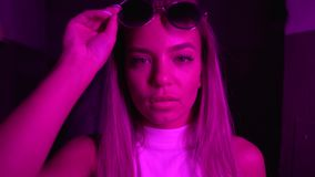 The girl looks at the camera, takes off and puts on sunglasses. Neon light.  stock video