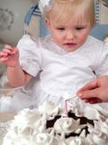 Girl looks at candle. On cake for birth day Royalty Free Stock Photo