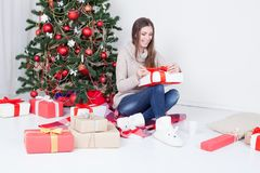 The girl looks Christmas gifts at the Christmas tree Royalty Free Stock Photos