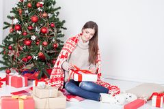 The girl looks Christmas gifts at the Christmas tree Royalty Free Stock Image