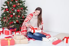 The girl looks Christmas gifts at the Christmas tree Royalty Free Stock Photo