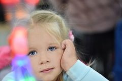 The girl looks at the colored light bulbs, dreams royalty free stock photos