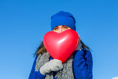 Girl looks covering face balloon in the shape of heart Royalty Free Stock Photos