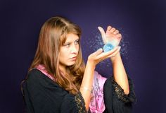 The girl looks in a crystal sphere. The girl with a shining sphere in hands royalty free stock photography