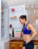 The girl looks curiously into the open refrigerator Royalty Free Stock Images
