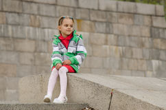 Girl looks into distance while sitting a granite embankment on ramp Stock Photography