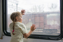 The girl looks into the distance from the window of a train car Stock Photo