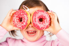 Girl looks through donuts Stock Photos
