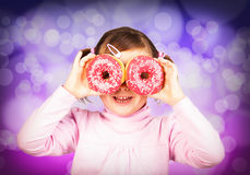 Girl looks through donuts Royalty Free Stock Image
