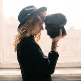 The girl looks in the eyes of the skull. Curly girl in a cap with a skull in her arms and a tattoo on her hand royalty free stock image