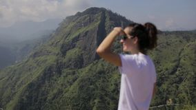 Girl looks at the forest valley from a top stock footage