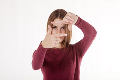 Girl looks in the frame of her hands stock photo