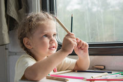 Girl looks funny on pencils at the table in the second-class train carriage Stock Photos