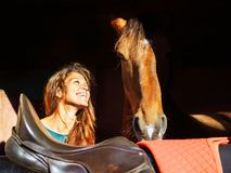 The girl looks at the head of a red horse with love royalty free stock photo