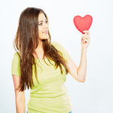 Girl looks at the heart which keeps in his hand. Symbol of love Stock Images