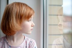A girl looks into her reflection in a window. A redhead girl looks into her reflection in a window royalty free stock photo
