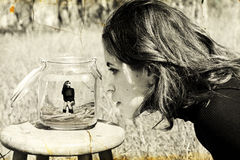 Girl looks at herself in the glass jar. royalty free stock image