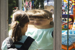 The girl looks at herself in the mirror