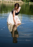 Girl looks at his reflection in the water Royalty Free Stock Images