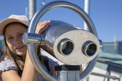The girl looks with interest at the telescope. Royalty Free Stock Photos